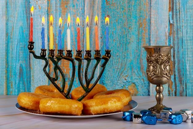 Menora z płonącymi świecami, pączkami i filiżanką wina