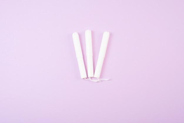 Menstruacyjne tampony na białym tle na różowym tle.