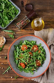Menu dietetyczne. kuchnia wegańska. zdrowa sałatka z rukolą, pomidorami i orzeszkami piniowymi. leżał płasko. widok z góry