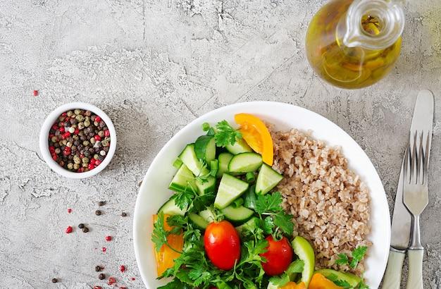 Menu dietetyczne. zdrowa sałatka wegetariańska świeżych warzyw - pomidorów, ogórków, słodkiej papryki i owsianki na misce. wegańskie jedzenie. leżał płasko. widok z góry