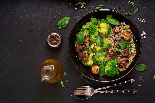 Menu dietetyczne. zdrowa wegańska sałatka warzywna - brokuły, pieczarki, szpinak i komosa ryżowa w misce. leżał płasko. widok z góry