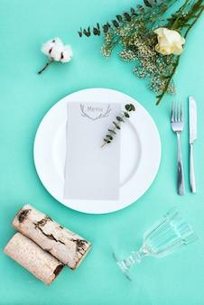 Menu kolacji na wesele lub luksusowy wieczorny posiłek. ustawienie stołu z góry. elegancki pusty talerz, sztućce, szkło i kwiaty