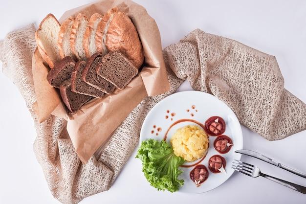 Menu obiadowe ze smażonymi kiełbasami, puree ziemniaczanym i fasolą podawane z kromkami chleba.