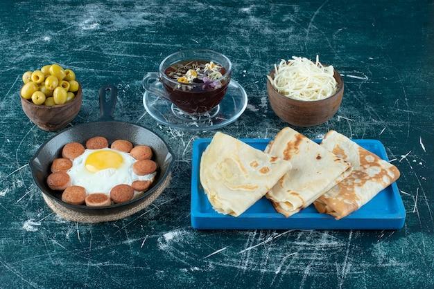 Menu śniadaniowe z naleśnikami, filiżanką herbaty i dodatkami. zdjęcie wysokiej jakości