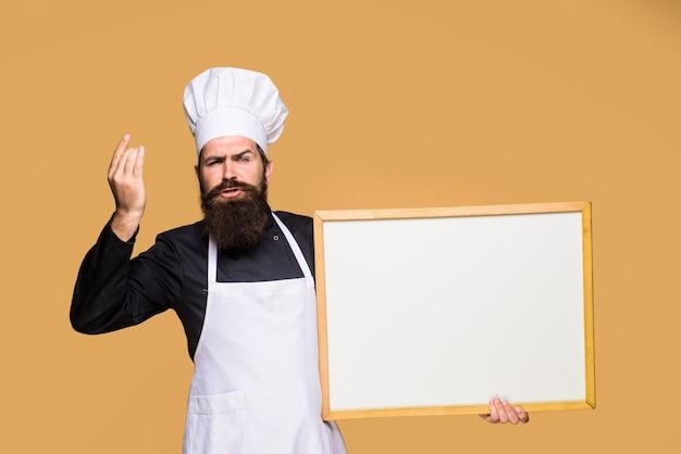 Menu szefa kuchni mężczyzna kucharz pokazuje pustą tablicę menu z reklamą miejsca na kopię szczęśliwy szef kuchni przytrzymaj
