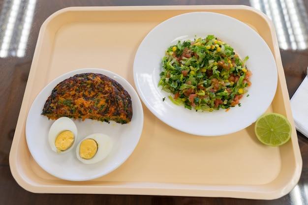 Menu tacek z omletem z marchwi jajko na twardo i talerze sałatkowe przerwa na lunch w koncepcji fabrycznej