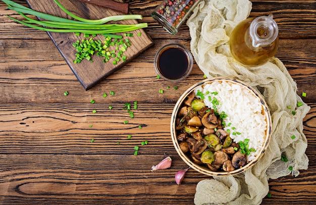 Menu wegańskie. żywność dietetyczna. gotowany ryż z pieczarkami i brukselką w stylu azjatyckim. widok z góry. leżał płasko.