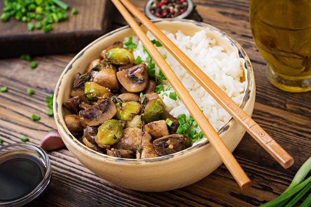 Menu wegańskie. żywność dietetyczna. gotowany ryż z pieczarkami i brukselką w stylu azjatyckim.