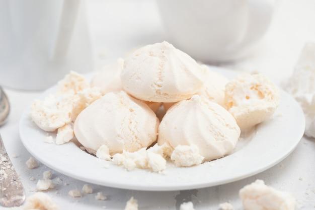 Merengues na bielu talerzu na biel powierzchni