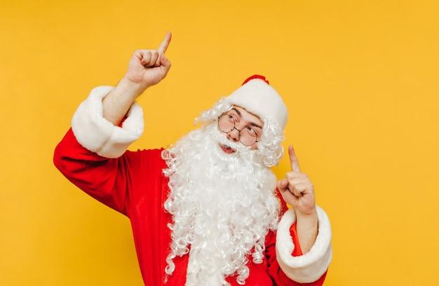 Merry santa claus robi awans i wskazuje palcami w górę