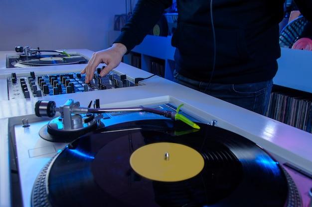 Mesa de dj con un tocadiscos que tiene un disco de vinilo naranja concepto de musica retro
