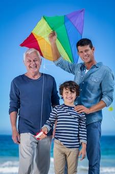 Męscy członkowie rodziny bawić się z latawcem