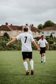 Męscy gracze futbolu na boisku piłkarskim