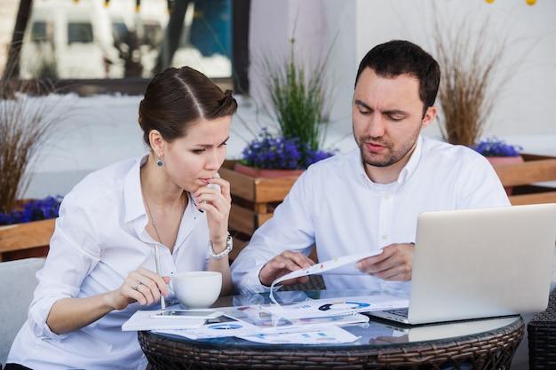 Męscy i żeńscy biznesowi koledzy pracuje wpólnie nad ciężkim problemem przy outdoors kawiarnią. mają napięty wyraz twarzy