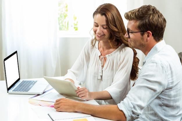 Męscy i żeńscy koledzy dyskutuje dokument przy biurem