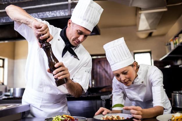 Męscy i żeńscy szefowie kuchni przygotowywa jedzenie w kuchni