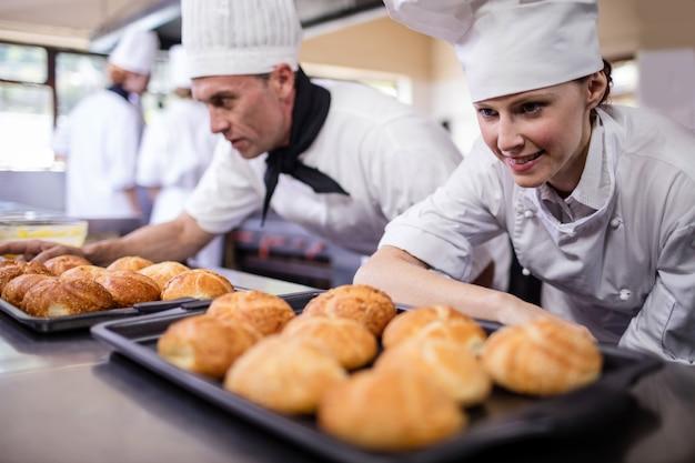 Męscy i żeńscy szefowie kuchni przygotowywa kaiser rolki w kuchni