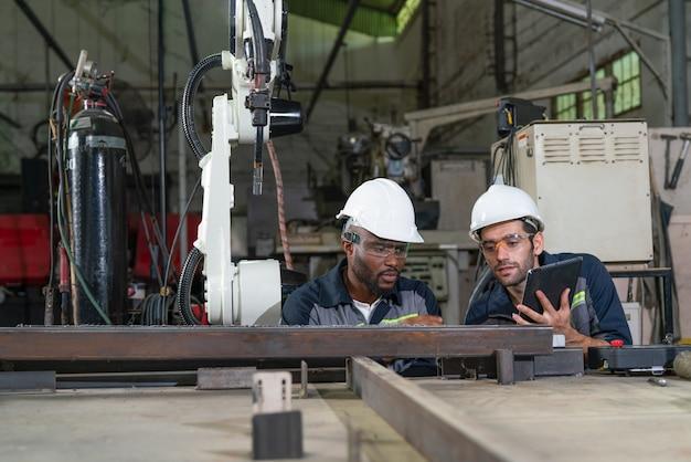 Męscy inżynierowie patrzący na spoinę na stali, która jest spawana przez maszynę z ramieniem robota w warsztacie fabrycznym