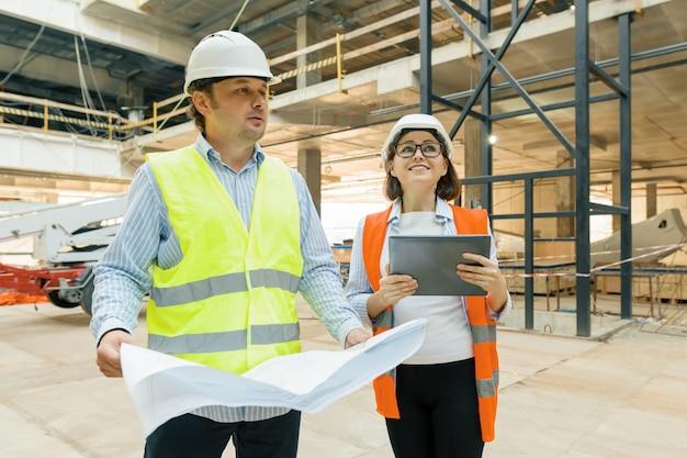 Męscy pracownicy budowlani pracuje przy budową, budowniczowie patrzeje w projekcie