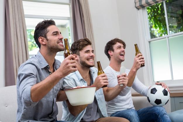 Męscy przyjaciele cieszy się piwo podczas gdy oglądający mecz piłkarskiego w tv