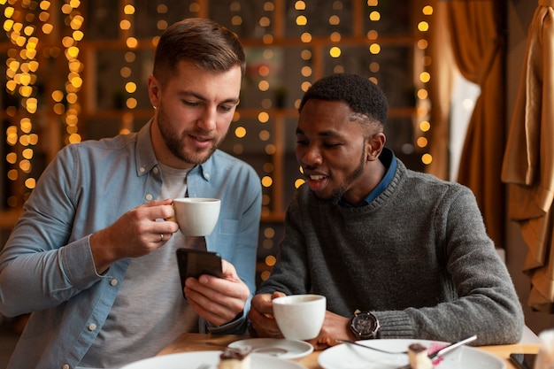Męscy przyjaciele patrzeje telefon