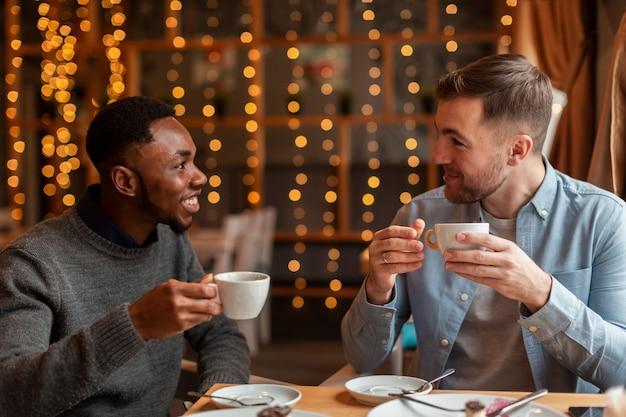 Męscy przyjaciele pije kawę przy restauracją
