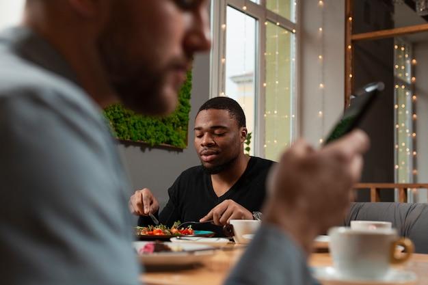 Męscy przyjaciele przy restauracyjnym jedzeniem