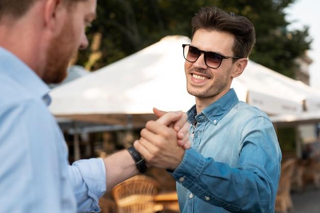 Męscy przyjaciele uścisk dłoni na zewnątrz