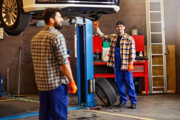 Męscy współpracownicy w serwisie samochodowym wspólnie pracują nad podniesionym samochodem