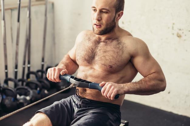 Męska atleta na wioślarskiej maszynie na przecinającej rywalizaci