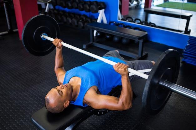 Męska atleta robi ławki prasie w sprawności fizycznej studiu