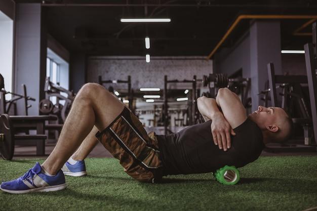 Męska atleta używa piankowego rolownika przy gym