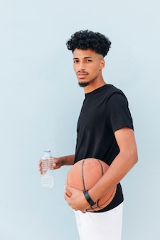 Męska atlety pozycja z koszykówką i plastikową butelką na miękkim błękitnym tle