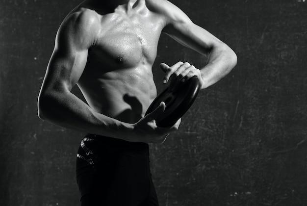 Męska, atletyczna budowa ciała przycięty widok ciemnego tła mięśni