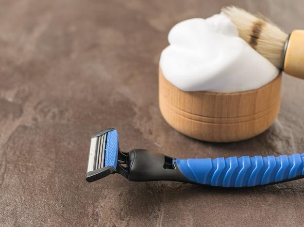Męska brzytwa, pędzel i pianka do golenia na kamiennym stole. zestaw do pielęgnacji męskiej twarzy.