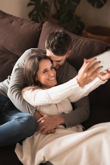 Męska całowanie kobieta podczas gdy brać selfie
