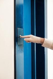Męska dłoń w rękawicy medycznej naciska przycisk w windzie