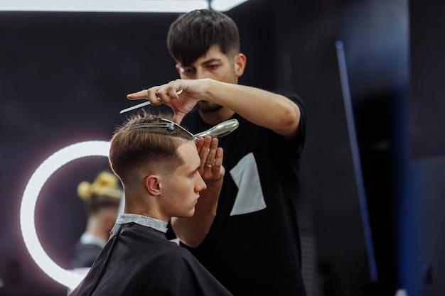 Męska fryzura z elektryczną maszynką do golenia. fryzjer wykonuje fryzurę dla klienta w sklepie fryzjerskim za pomocą strzyżenia włosów. fryzjerstwo męskie z golarką elektryczną.