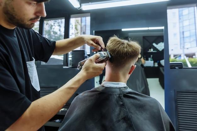 Męska fryzura z elektryczną maszynką do golenia. fryzjer wykonuje fryzurę dla klienta w sklepie fryzjerskim za pomocą strzyżenia włosów.