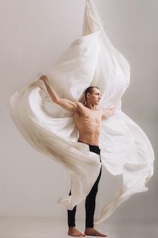 Męska gimnastyczka pozuje z powietrznymi jedwabniczymi faborkami