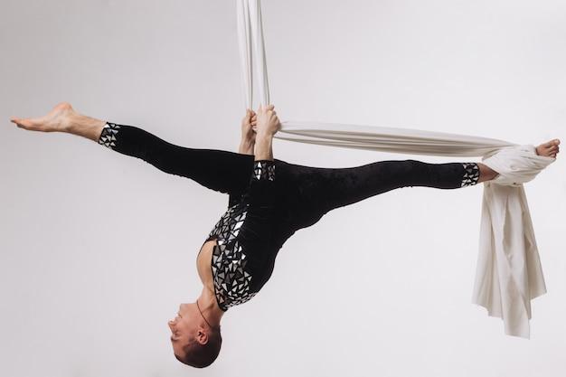 Męska gimnastyczka robi powietrzne akrobacje jedwabne