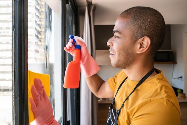 Męska gospodyni czyści szklanego okno w domu.