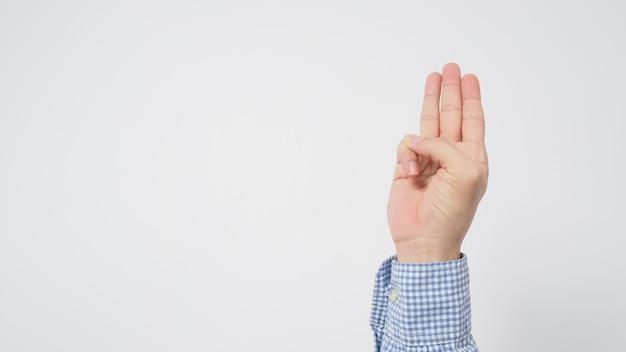 Męska koszula z długim rękawem robi znak ręki z trzema palcami skierowanymi w górę, co oznacza trzy, trzeci lub używany w proteście.