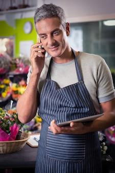 Męska kwiaciarnia bierze rozkaz na telefonie komórkowym