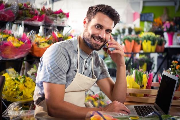 Męska kwiaciarnia opowiada na telefonie komórkowym podczas gdy używać laptop