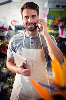 Męska kwiaciarnia opowiada na telefonie komórkowym