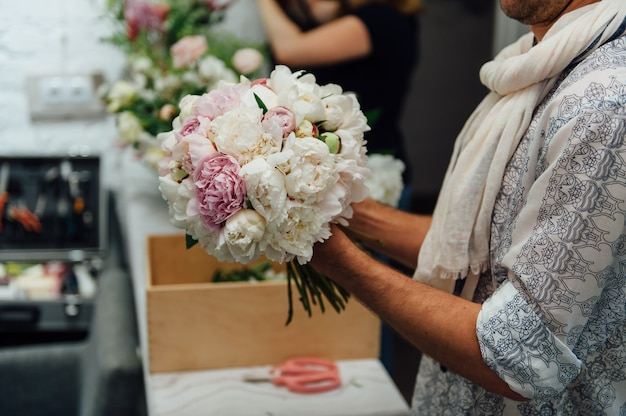 Męska kwiaciarnia przygotowywa bukiet peones