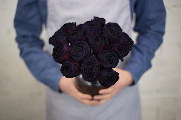 Męska kwiaciarnia trzyma jaskrawego kolor róży bukiet w ręce w fartuchu