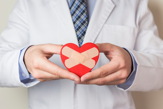 Męska lekarka pokazuje czerwonego serce z skrzyżowanym bandażem w ręce
