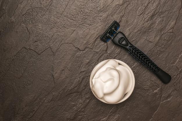 Męska maszynka do golenia i pianka do golenia na kamiennym stole. zestaw do pielęgnacji męskiej twarzy. leżał na płasko.